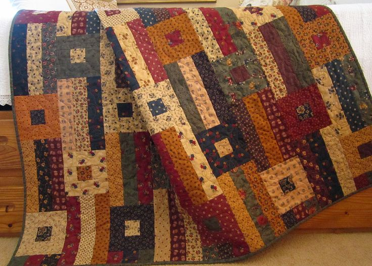 Relax and sit by the fireplace under this patchwork quilt. The colors are blue, tan, burgundy, green, purple, and gold. Many of the fabrics are from Moda's Kansas Trouble collections. There are flowers in many of the pieces used in this quilt. A great quilt for the bedroom, den, living room or on the porch.