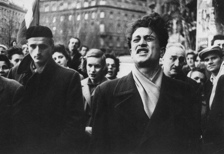 """Photograph by Michael Rougier. """"A Hungarian man sings a patriotic song as Soviet tanks move into Budapest during the 1956 Hungarian Revolution."""""""