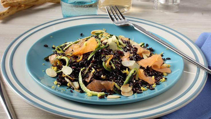 Cuoci il riso venere in abbondante acqua salata aggiungendo una foglia di alloro. Nel frattempo taglia il salmone a pezzetti e la zucchina a julienne sottili. Lava e pulisci i fiori di zucca e tagliali in quattro parti. Fai soffriggere in una padella l'ag
