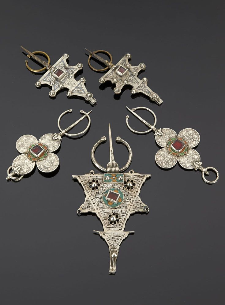 Morocco - Central Anti Atlas region.   Set of matching fibulae; copper, silver and glass. A set of matching silver fibulae made from joining four coins, enamel and glass details. A large silver, enamel and glass fibulae   Est. 300 - 400€ for the lot ~ (May '15)