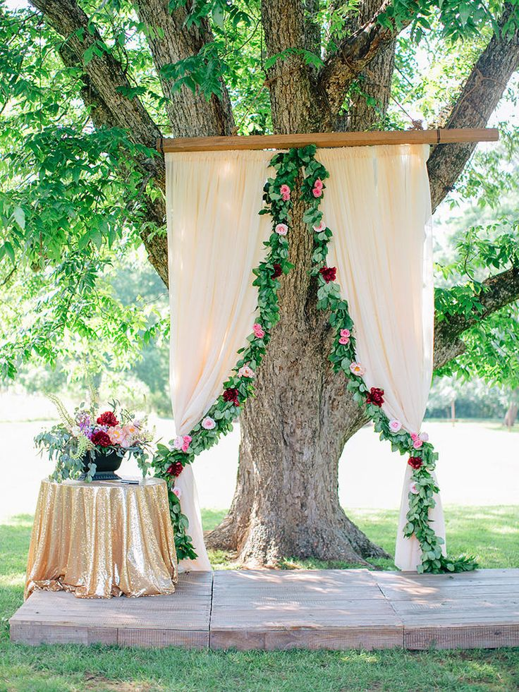 Outline fabric curtains with floral garlands for decorations suitable to a rustic, outdoor wedding ceremony.