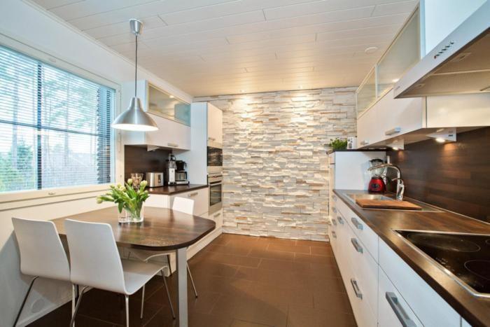 Keittiössäkin voi tehosteseinässä käyttää kiveä. Ruskea välitila, taso ja pöytä tekevät ilmeestä yhtenäisen.