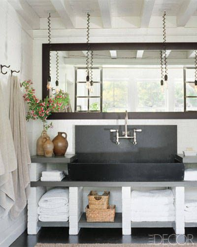 The master bath's vintage pendant lights hang above a breathtaking antique soapstone basin.