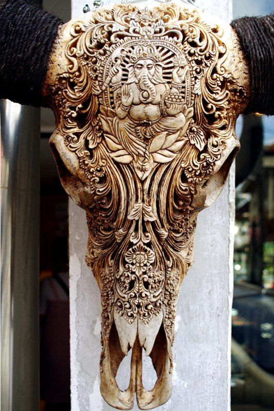 Close-up of an intricately carved water buffalo skull found on display in Ubud, Bali, Indonesia. The carving portrays the Hindu god of knowledge, Ganesha.