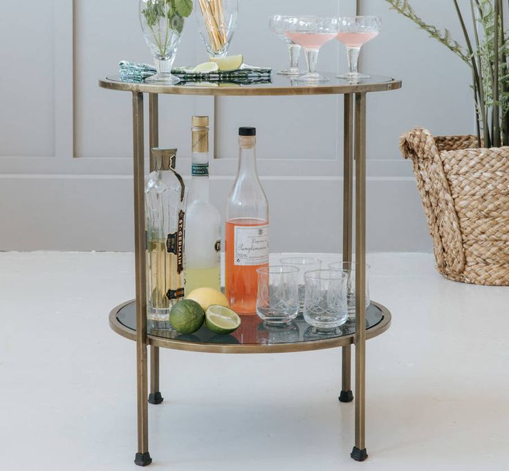 Standing on three legs, the two tiers are fitted with black glass panels, providing the perfect space to display your favourite glasses and bottles.We're huge advocates of having a drinks trolley in your home for those times when you have guests and want to show off your cocktail-making skills! If you don't have room for a trolley, or if you already have a trolley and would like to make more of a bar area in your home, this beautiful two-tiered glass side table is the perfect addition to…