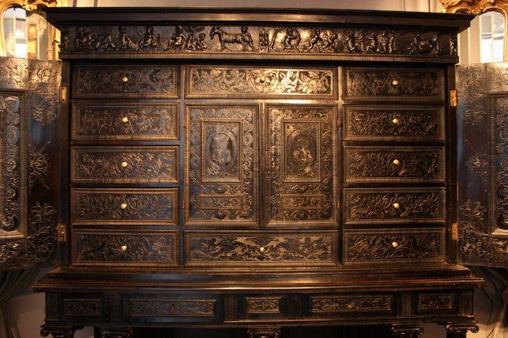 """Этот шкаф открывается две двери раскрывая двенадцать ящиков и две маленькие двери. Сцены, вырезанные на дверях изображены: """"встреча Давида и Авигеи"""" и """"Эстер и Assuerus"""". Гравировка используется в качестве модели выступили Швейцарский Matthaüs гравер Мериан, опубликованные в период между 1625 and1630 в Страсбурге."""
