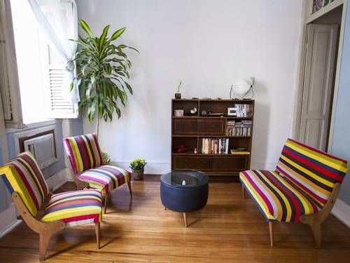 Sala de estar da casa de Maria Archer com conjunto de sofá e poltronas de pés-palito, mesa feita com pneu de carro de corrida e estante dos...