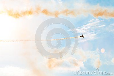Aircraft on air show with smoky trail. Airplane performing difficult maneuver in the sky. White clouds on blue sky background and smoke trail.