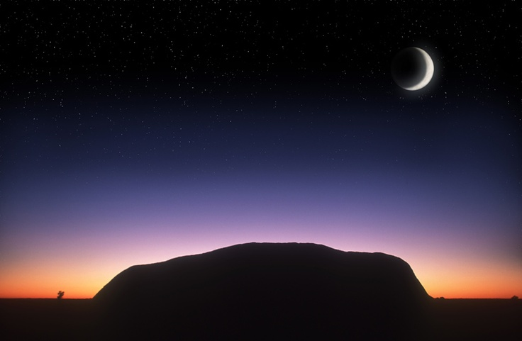 Silhouetted Ayers Rock at sunrise. Uluru, Australia.  Image by Martin Harvey / Peter Arnold / Getty