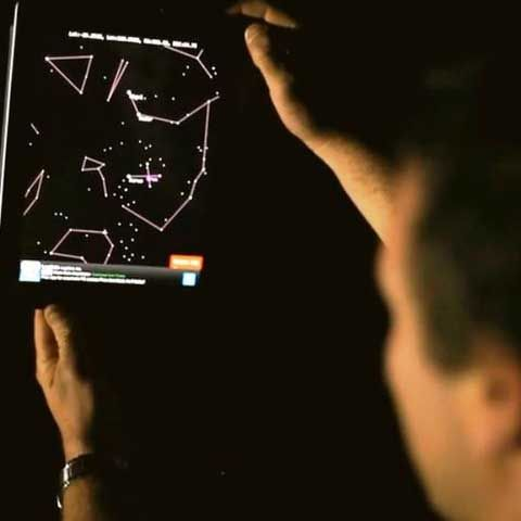 Voyages OSJ Man Looking at Night Sky Through the iPad