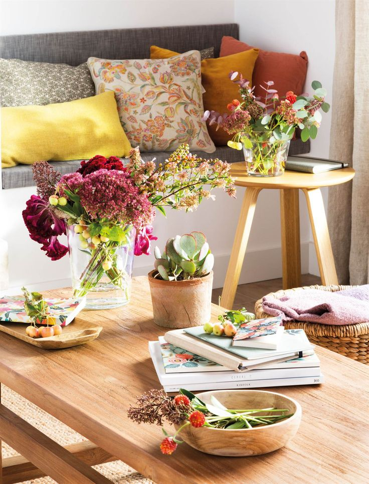 00469012. Mesa de centro de madera con jarrón y bol con flores. Al fondo, sofá con cojines 00469012