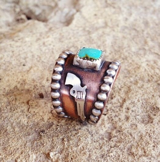 I don't like the pistol on the side but love the turquoise and colors on this ring.