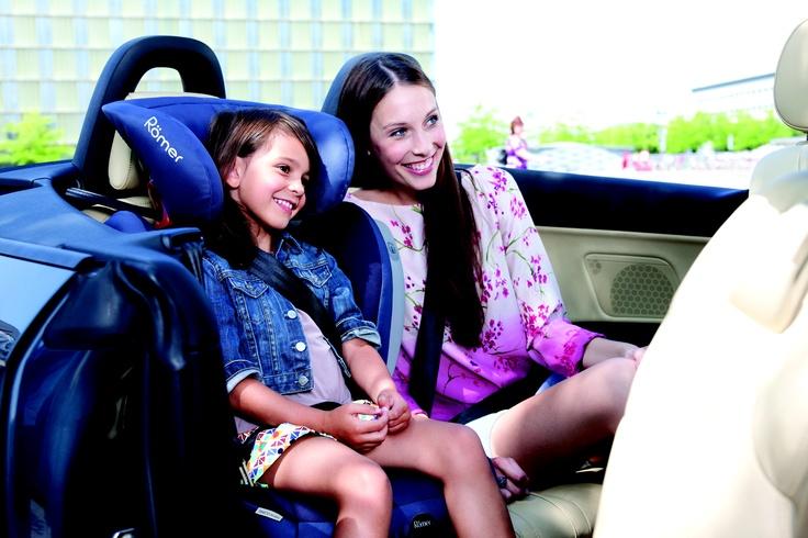 madre con hija sobre Römer Kidfix en el asiento trasero de un descapotable