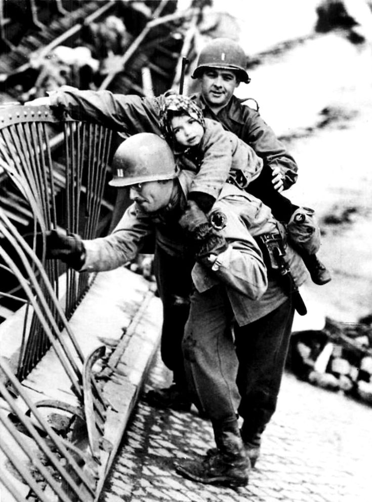 U.S. Army Cpt. J. McMahon and an unidentified American soldier of the Ninth United States Army carry a small German girl across the destroyed bridge at Tangermünde, over the River Elbe. The bridge had been blown up by the retreating Germans to stifle...