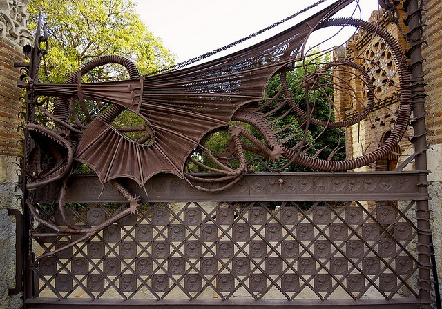 Iron gate with mytical drago designed by Antoni Gaudi. Located Pavellons Güell, Barcelona.