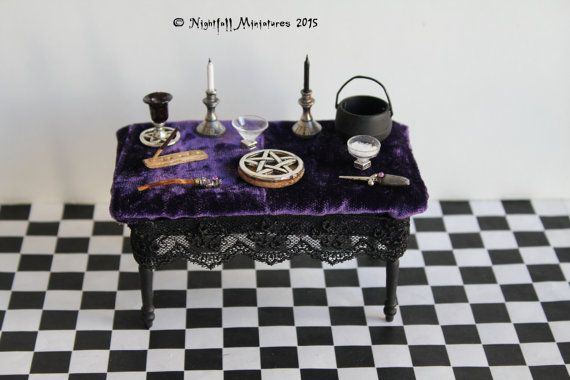 Een houten Wicca pagan altaar tafel met paars fluwelen tafellaken. Bevat zwarte en witte kaarsen, pentagram, paarse goblet met pentagram