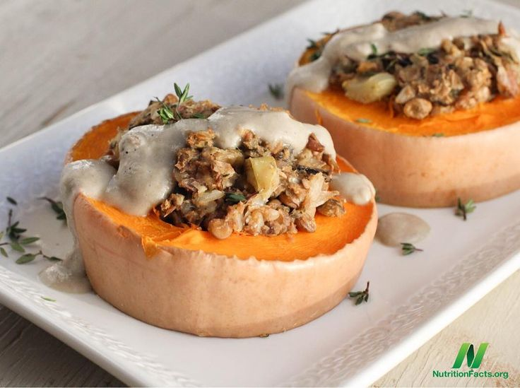 Butternut squash with lentil and wild rice stuffing. Topped with creamy mushroom gravy. #plantbased #wholefoods