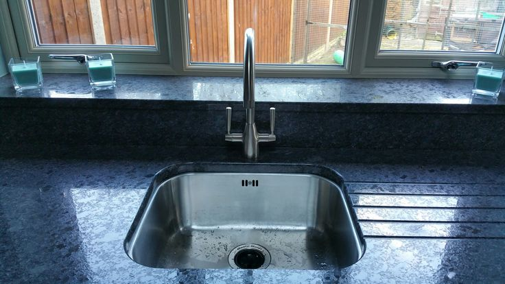 Bluci Rubus 50u under mounted kitchen sink with granite worktops and drainer grooves. This customer has also fitted a waste disposal unit to the sink (as shown by the black plug).  The Granite worktop has also been set slightly back from the edge of the sink.  Some customers set the worktop with an overhang to help the water drain back into the bowl from the drainer grooves.  Thanks for sending the image to us.