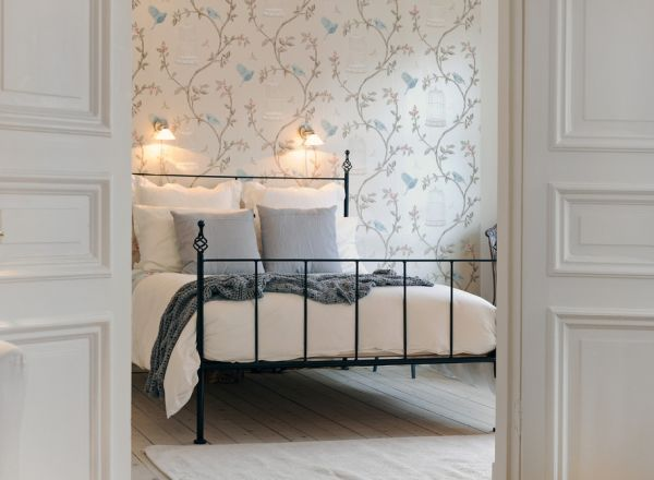 Cozy and inviting bedroom with elegant wallpaper and metal framed bed