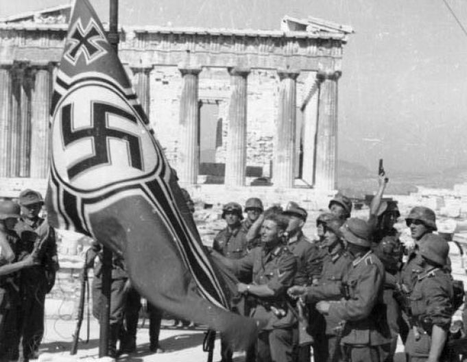 German soldiers raise their flag over the Acropolis in Athens, Greece (1941). Note the soldier on the right background apparently firing his pistol in celebration.