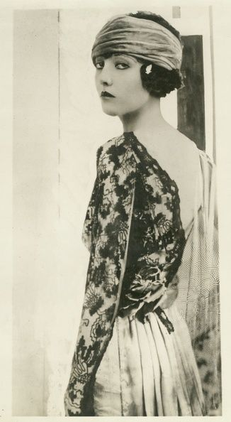 This picture was photograph in 1919, that means this time prepared change into totally new fashion look. Hair was cut off with a turban,wear a heavy make up face, wear backless top. And this is a flapper 's image, what became popular during 1920s