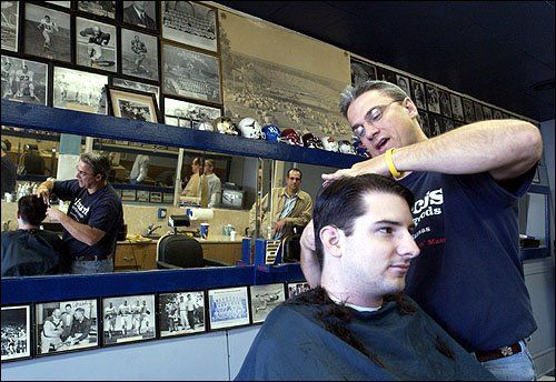"""Rex's Stadium Barber Shop, 1033 Massachusetts Ave, Lawrence, Kansas. It's been some variant of """"Stadium Barber Shop"""" since 1923. Present owner Rex Porter (above), formerly with Downtown Barber Shop, bought this place in 2004 from RC Pewtress, proprietor since 1987. Rex has kept it as a Kansas Jayhawks sports shrine. [Scott McClurg photo]"""