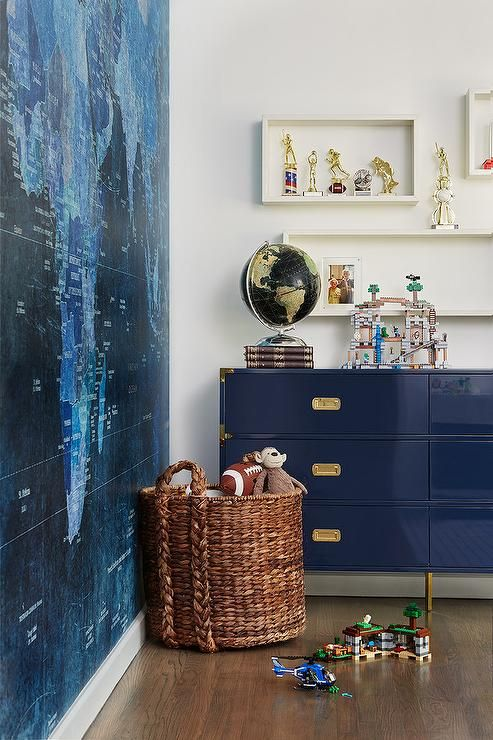 Contemporary boy's room features a navy blue lacquered campaign dresser placed beneath staggered white box shelves mounted on a white wall as a woven toy basket sits in front of a wall covered in a blue world map mural.