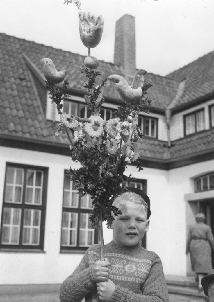 Mit Buchsbaum, Süßigkeiten, einem Apfel und Gebäck in Vogelform ist der Palmstock dieses Jungen aus Anholt (Kreis Borken) im Jahre 1957 prächtig geschmückt. Foto: LWL-Archiv/Schlechtriem