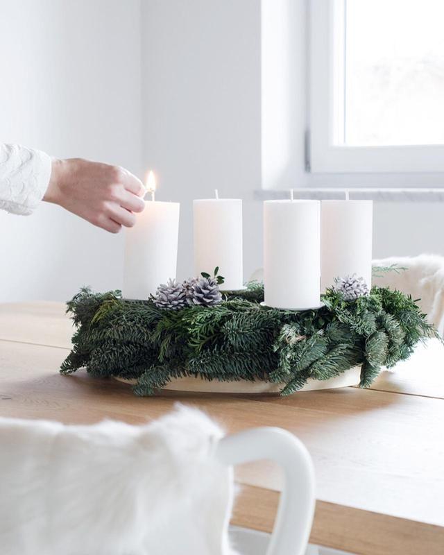 Ein Adventskranz mit viel Grün und weißen Kerzen auf einem Holzteller. Klassisch und immer wieder schön anzusehen. #advent #weihnachten #skandinavisch #kerzenschein #xmas