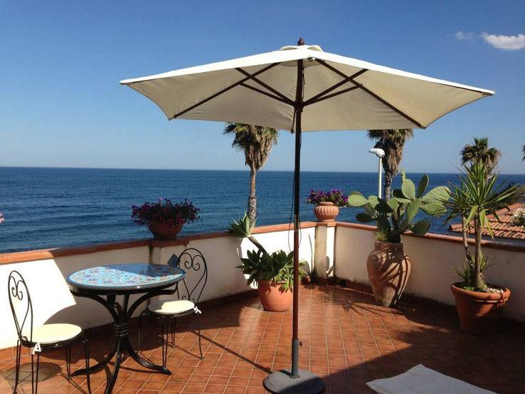 Terrasse avec vue sur la mer : parasol, cactus et petite table en mosaïque