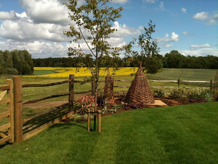 View of the newly created planting border, specimen trees & children's woven willow play house - materials were carefully chosen to be in keeping with the beautiful rural surroundings.