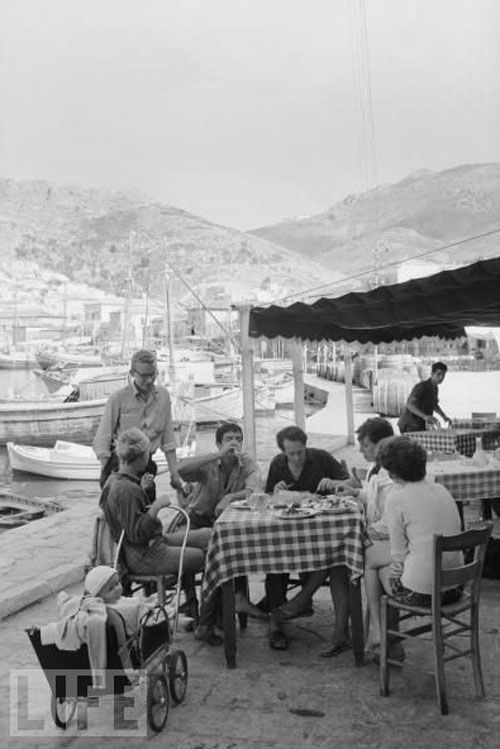 Leonard Cohen with Marianne Ihlen, her partner Axel Jensen and others outside Katsikas' grocery store/taverna on Hydra's port. The man seated next to Cohen is George Johnston Australian author (My Brother Jack). The woman second from the right is Charmian Clift (Australian author, George's wife). Marianne's son Axel is in the baby carriage. Hydra – Oct 1960
