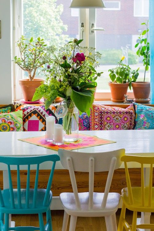 so cute! I really like the different coloured chairs, the beautiful abundance of plants, and the multicoloured and patterned cushions!