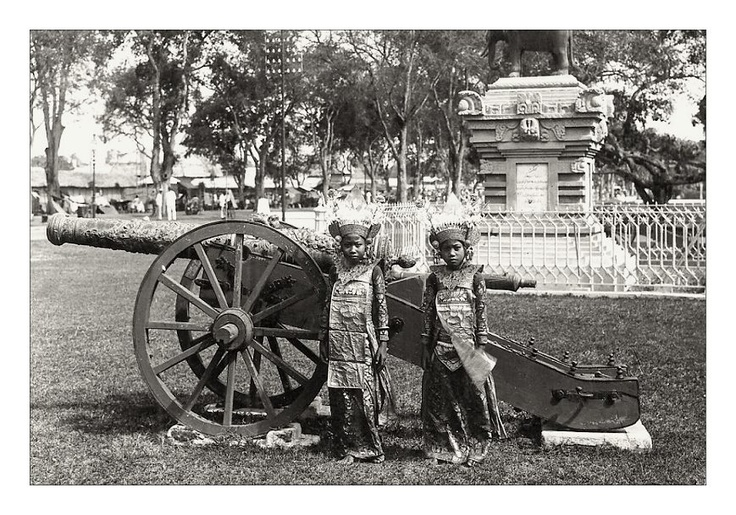 Two Balinese Legong dancers pose in front of a cannon, old Dutch postcard, 1920s
