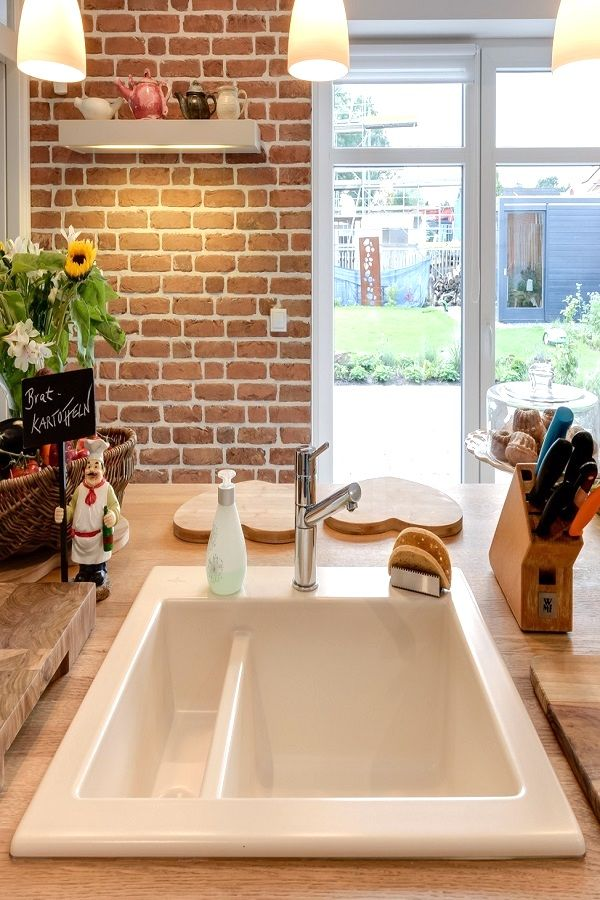 Elegantes Spülbecken aus Keramik in einer Landhausküche. Mit ...