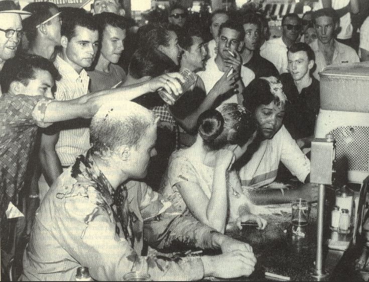 Sit-in at the Woolworths lunch counter in Jackson, Mississippi, 1963.  Annie Moody (far right) was a student at Tougaloo College in Jackson. Mustard and ketchup drip off her forehead.JoanTrumpauer (center), a white student at Tougaloo, had been doused with mustard, ketchup, water, Coca-Cola, and spray paint. Tougaloo professor John Salter (left) is covered in condiments and blood. He had been hit with brass knuckles.