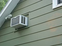 Installing a window air conditioner in a hole in the wall.