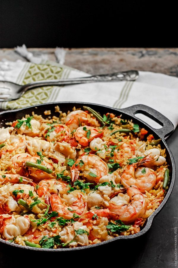 Seafood Paella - Lobster tails, water, olive oil, onion, Spanish rice or short grain rice, garlic, saffron, paprika, cayenne pepper, aloppo pepper flakes, salt, tomatoes, green beans, shrimp and parsley