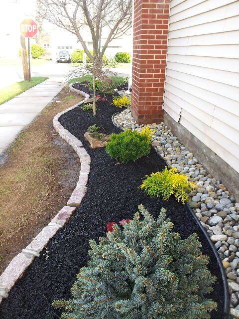 On the side of your home: Use curbing (Belgian Block used here), your plants/bushes and mulch, some black edging, and finally some rock/stone (Delaware stone used here) against your house to drain it well & keep termites & other bugs from coming in the house!