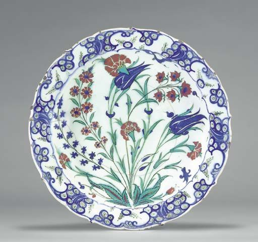 AN IZNIK POTTERY DISH  OTTOMAN TURKEY, CIRCA 1570  With cusped sloping rim on short foot, the white interior painted in blue, green, black and red with a central carnation piercing a tulip flowerhead flanked by an asymmetric arrangement of further carnations, another tulip, hyacinths and other flowers all issuing from a central tuft, the rim with stylized blue wave and rock design, the exterior with alternating paired tulips and flowerheads, rim slightly fritted,   11¾in. (29.6cm.) diam.
