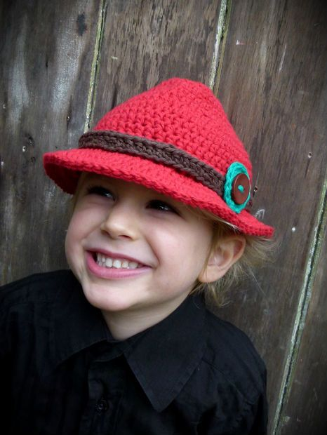 Add some attitude with this wicked bright red fedora hat!  Complete with a chocolate brown band & emerald circle topped with a large brown button, this wee beauty is sure to put a smile on your little man & all those around :) This hat has been lovingly made in a tight stitch to provide a firmer shape, though it is still soft and flexible for comfort too.  Handmade in NZ using 100% cotton.  www.facebook.com/media/set/?set=a.380721155365354.1073741832.380252362078900&type=3