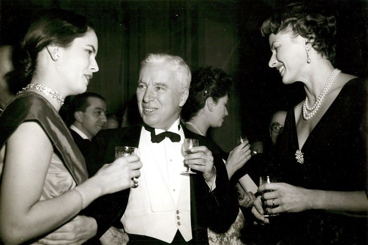 """Rome, Italy December 1952 """"Charles Chaplin and wife, Oona (to his right) and actress Ingrid Bergman (to his left) at a dinner party in Charlie Chaplin's honor at a fashionable hotel in Rome. Charlie Chaplin was made a grand officer of the Italian Legion of Merit at the dinner. The award was presented by Giulio Andreotti, undersecretary of the council of ministers in charge of the entertainment industry in Italy."""""""