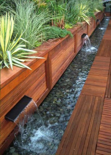 """Raised beds that allows water overflow to pour into a """"river."""""""