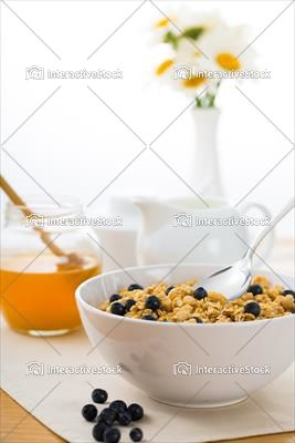 Śniadanie na zdrowie. Płatki, miód, mleko, jagody i płatki.