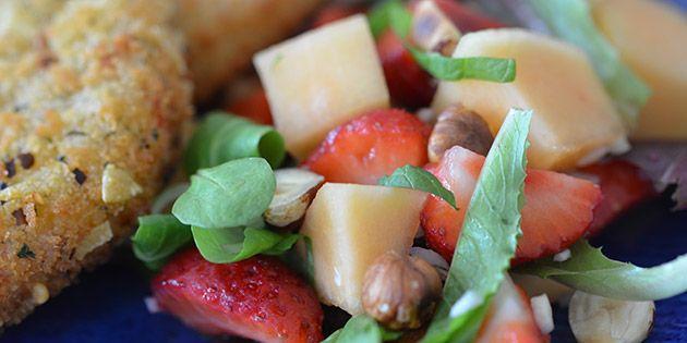 God salat med sødmefulde jordbær og melon samt ristede nødder og et friskt strejf af mynte.