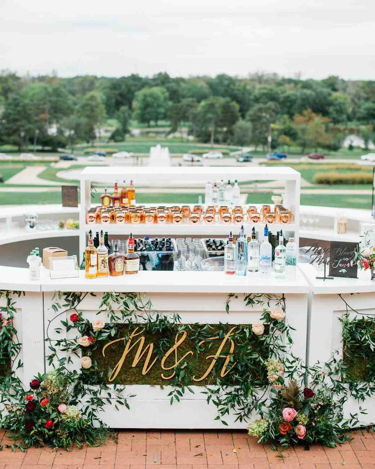 A Tuscan-Inspired Affair in St. Louis, Missouri | Martha Stewart Weddings - Cocktail hour took place on the lower level of the World's Fair Pavilion. The round bar served as the centerpiece for the evening, and was styled with flowers and the couple's monogram.