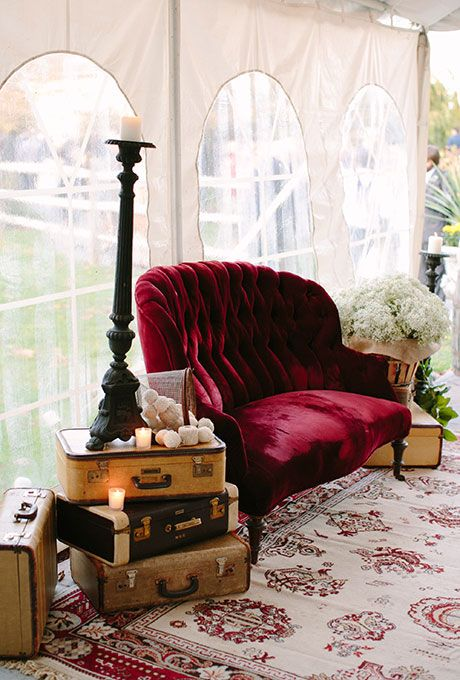 A cozy, vintage-inspired seating area with velvet couches and antique luggage | Brides.com