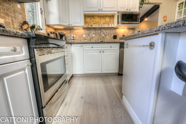 The kitchen of this beautiful Home features Lauzon Flooring Fifth Avenue Wire Brushed hardwood flooring from the Urban Loft Series. #interiordesign #hardwoodfloor #artfromnature #kitchen