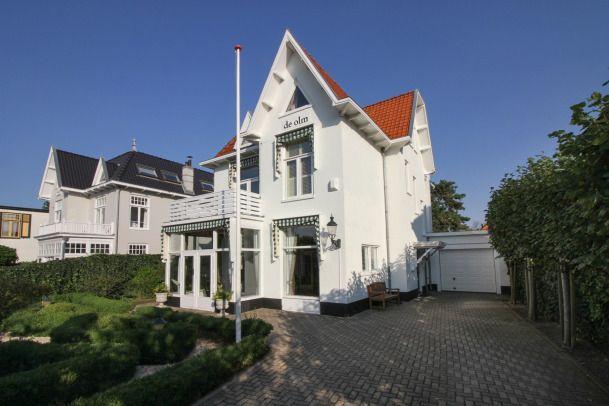 """Kostverlorenstraat 119; Deze karakteristieke en zeer goed onderhouden vrijstaande villa """"De Olm"""" uit 1912 met o.a. 6 royale slaapkamers, 2 badkamers, diverse woon-, eet- en zitgedeeltes, garage, oprit voor meerdere auto's en een royale tuin rondom is gelegen in het geliefde """"Groene Hart"""" van Zandvoort."""