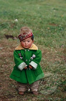 SuperStock - China, Children, Portrait Of Young Kazakh Child Wearing Green Wool Coat And Embroidered Cap.